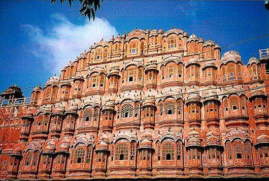 "Hawa Mahal or the : ""Palace of Winds"" is a narrow palace, almost a facade, with 953 small windows called jharokhas decorated with intricate latticework. The original intention of the lattice was to allow royal ladies to observe everyday life in the street below without being seen, since they had to observe strict ""purdah"" (f"
