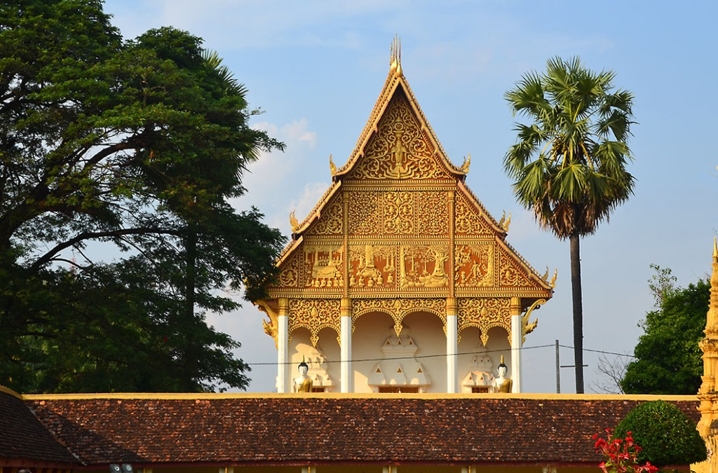 View of the red and gold decorateive pediment of the sentinel shrine of Wat That Luang Neua from the courtyard of Wat That Luang