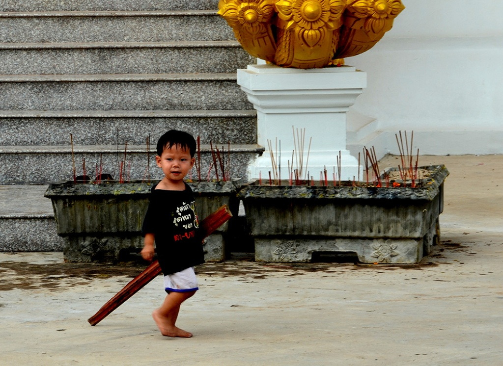 The cute little Wat keeper's son with a stick in his hand.