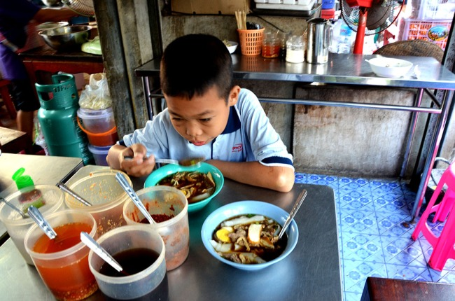 Boy having lunch Maeklong railway market in Bangkok