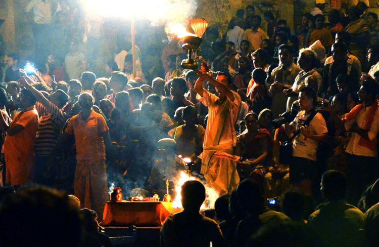 Temple priest holding up a lighted brass lamp with cobra hood amid hordes of devotees.