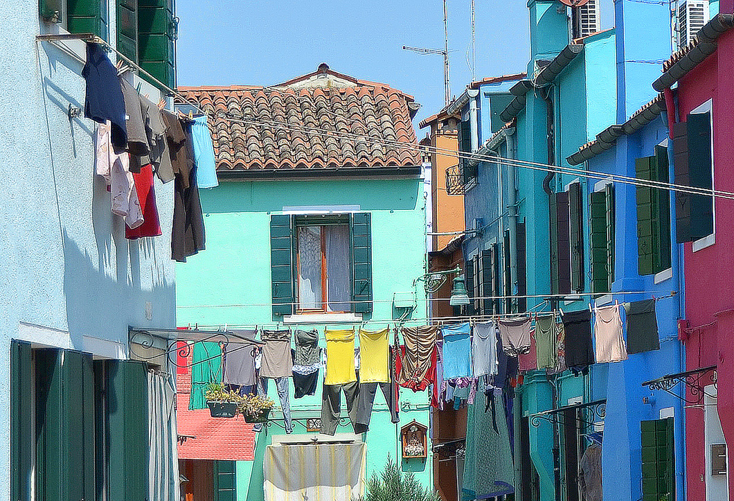 Colourful clothes on a line against aqua green and a blue walls.