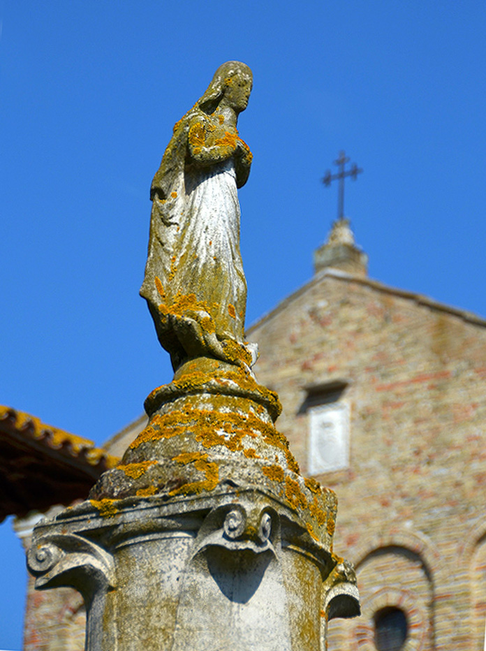 Close-Up of the moss covered statue of Santa Maria on top of a pedestal in front of Torcello Cathedral