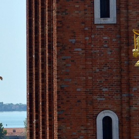 Two of three sword wielding golden lion heralds atop red flag posts in Piazza San Marco.