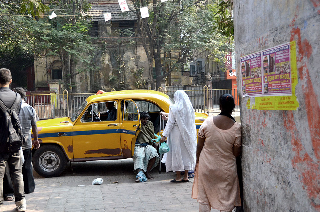 Sisters from the Missionaries of Charity foundation helping a sick man into a taxi.