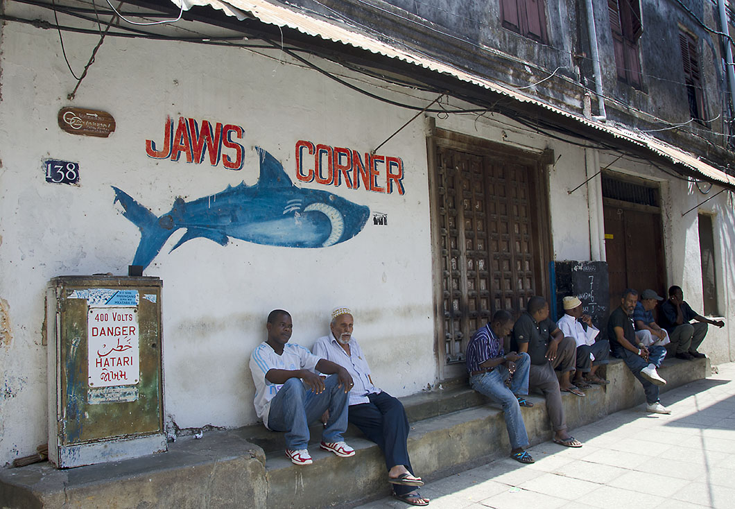 Local men seated beneath the shark mural that gives Jaws Corner its name - Stone Town Travel Guide