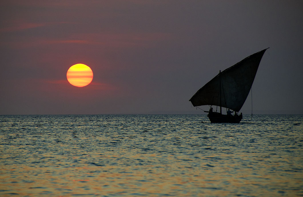 Zanzibar sunset - Silhouette of sail boat and golden orb of the setting sun.