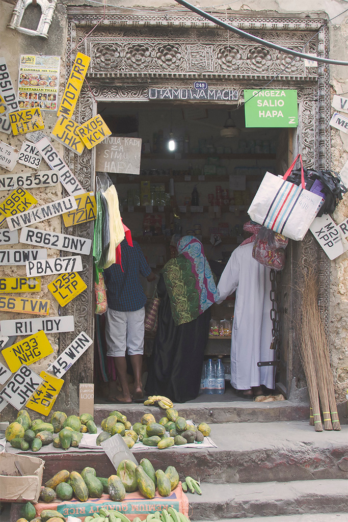 Shop in Zanzibar with ornate door and yellow car number plates on a wall on the left