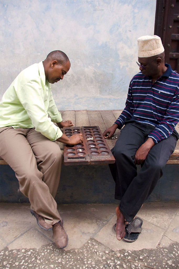 Two local men playing the traditional game of Bao - Stone Town Travel Guide