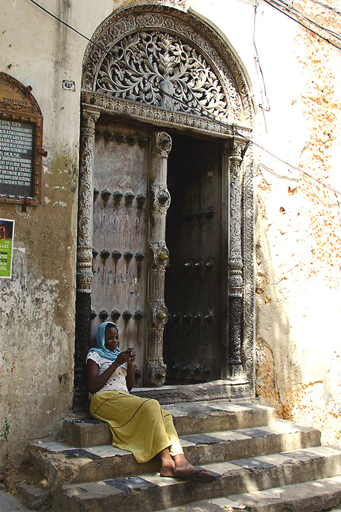 Young girl in a yellow skirt on the steps of slave trader Tipu Tip's house with the ornate door behind her - Stone Town Travel Guide
