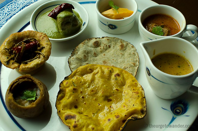 Clockwise from left: Baati (Traditional flour pastry filled with dhal), Gatta Tart (Chickpea flour tarts) filled with Ker Sangri, Dhania Murgh (Chicken morsels cooked with corriander seeds), Pithod Saubzi (Cooked gramflour and yoghurt cut into diamond shapes), Laal Maans (Lamb cooked in yoghurt and chili gravy), Dal Panchmel (Mélange 0f five lentils seasoned with asafoetida) Missi Roti (Chickepea flour bread) Bajra Roti (Millet bread)
