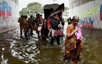 Chennai: People move from their waterlogged houses following heavy rains in Chennai on Tuesday. PTI Photo (PTI11_17_2015_000183B) via Indian Express