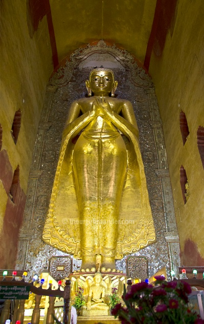 """One of two original 11th century 9.5 mt tall standing Buddhas in the Ananda temple. This faces North. Two more replicas face East and West. Ananda Paya is considered the """"finest, largest, best preserved and most revered of Bagan temples."""". The crowds are proof."""