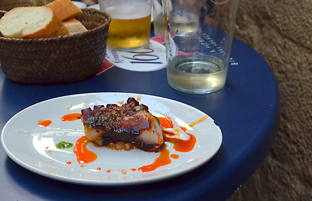 Char grilled octopus pintxo on a white plate placed on a blue painted table. San Sebastian