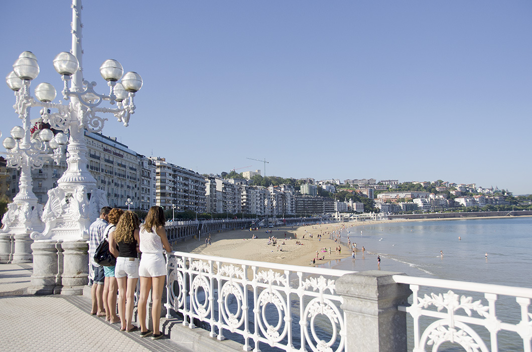Four tourists stand in front of the signature white railing and lamp post along the beach in San Sebastian.