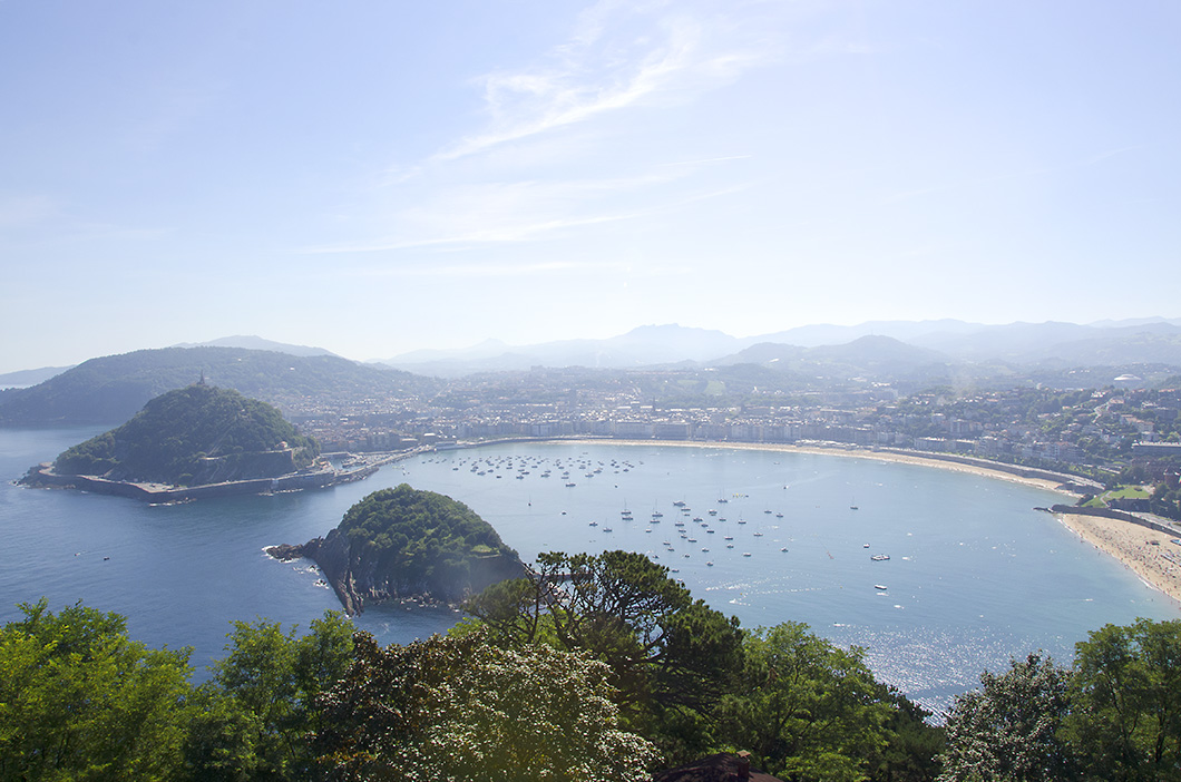 Panorama from the top of Monte Igueldo. The two wooded islands are visible far below and a hazy skyline beyond.