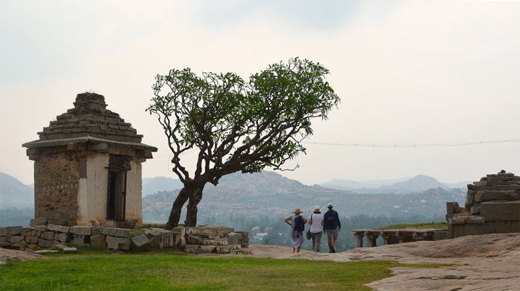 Three tourists on Hemakuta hill in Hampi - Header Image for Travel Stories Page