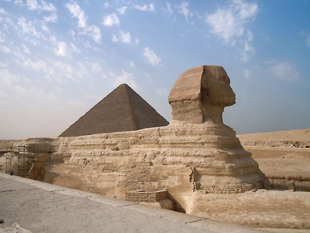 Side view of the he Sphinx with the Great Pyramid of Giza in the background.