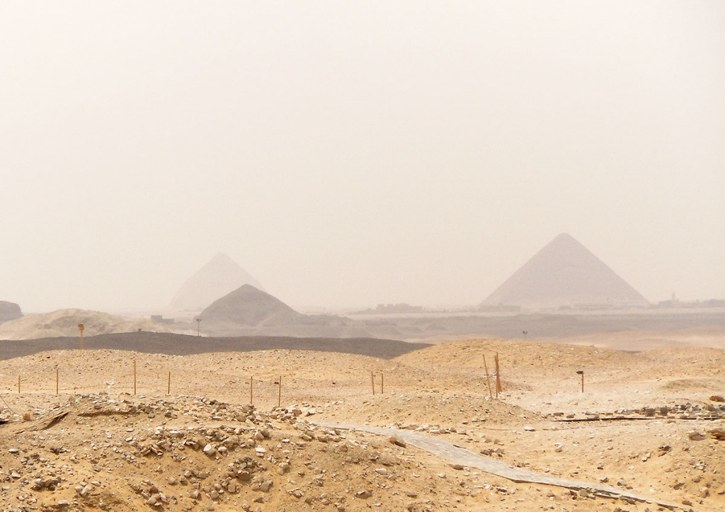 Hazy view of the Bent Pyramid and all the way to the Pyramids of Giza from high above the Red Pyramid.