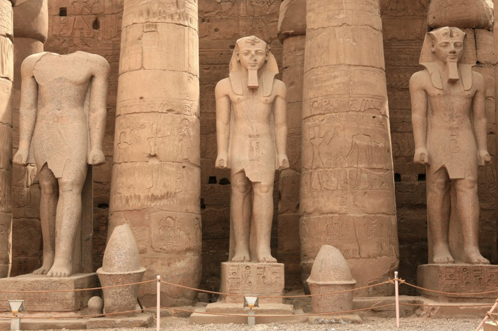 Three of the colossal statues lining the Great Court of Ramesses II in Luxor Temple.