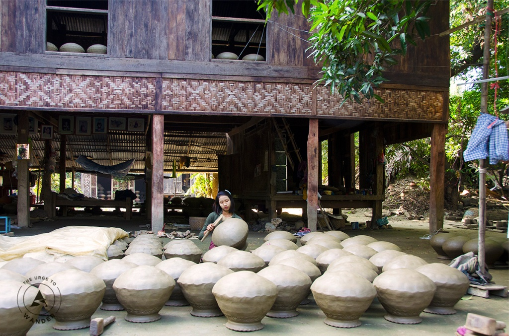 A young girl tests rows of overturned clay pots by tapping with a wooden stick in Yandabo