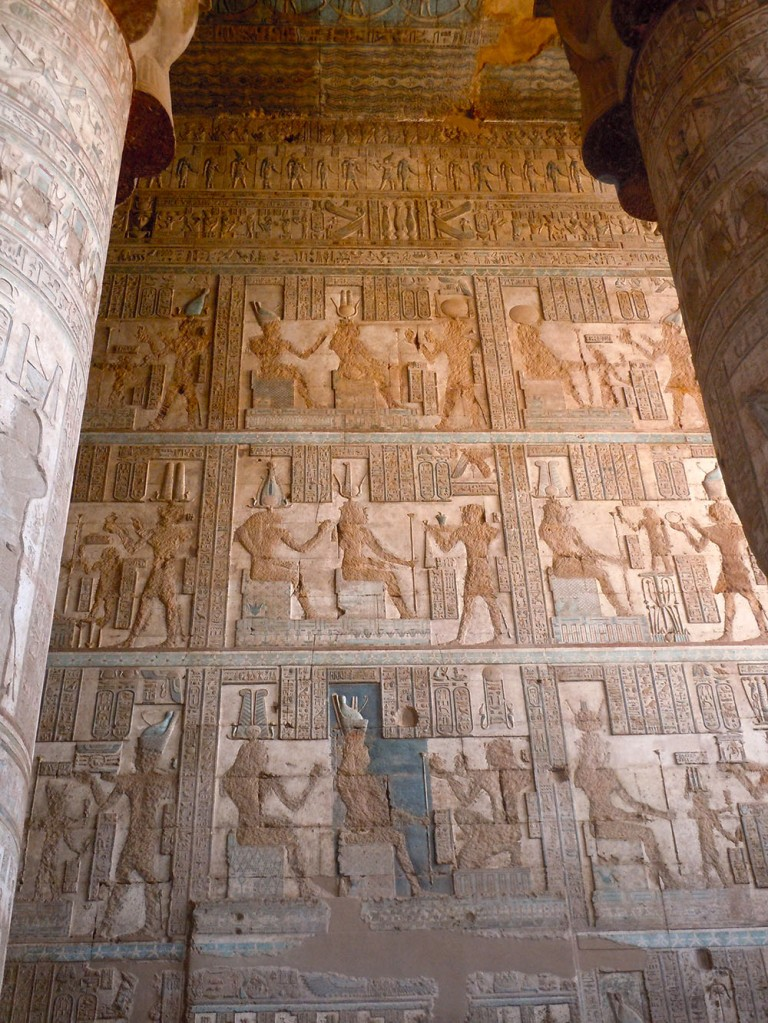 Entire wall covered with square relief panels depicting pharaohs making offerings to gods