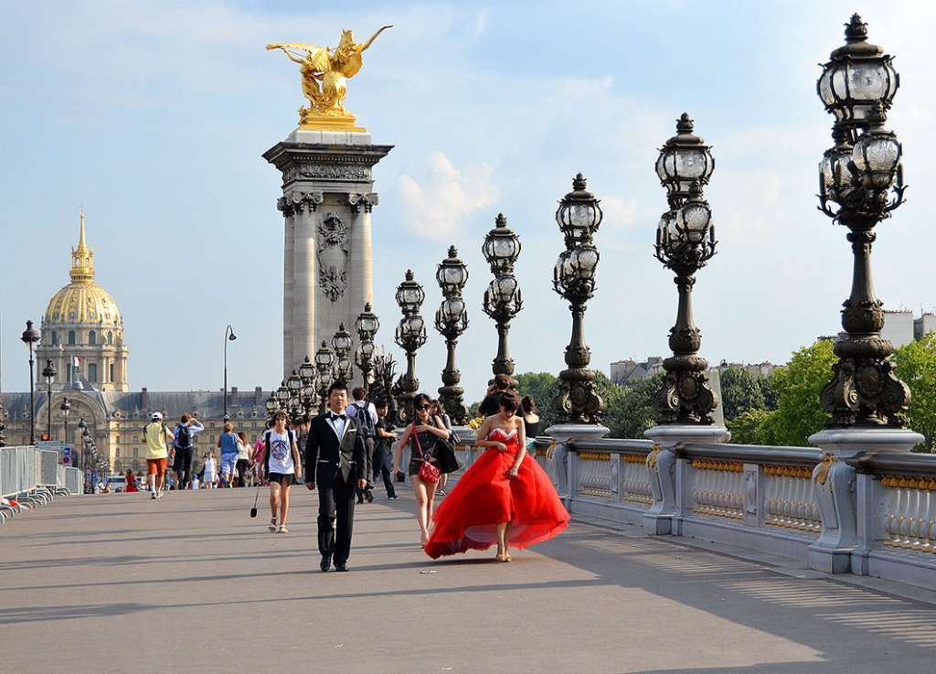 Bride in a red flowing dress on the Pont Alexander III, Paris