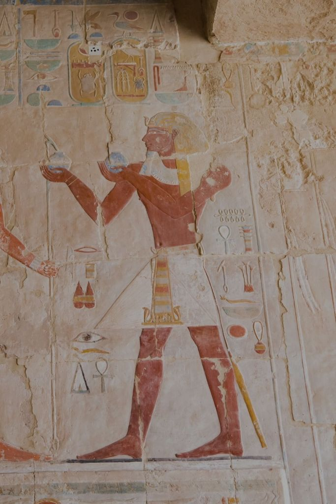 Wall mural depicting Pharoah Tuthmose making an offering to the Horus (not in frame) in Deir el Bahri, Luxor, Egypt
