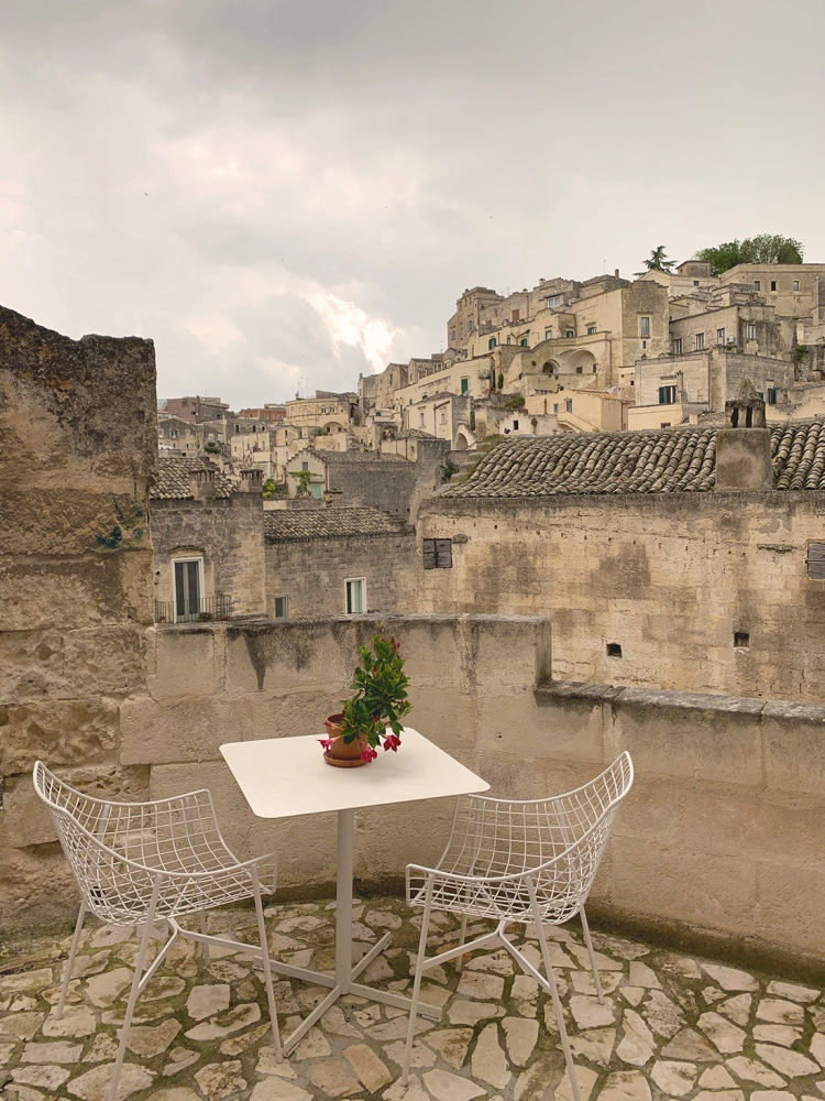 White metal wire chairs and table on a terrace with view of the Sassi of Matera.