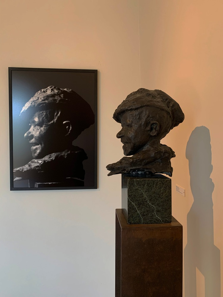 Bronze sculpture by Medardo Rosso on a pedestal juxtaposed against its photo on the wall in MUSMA, Matera.