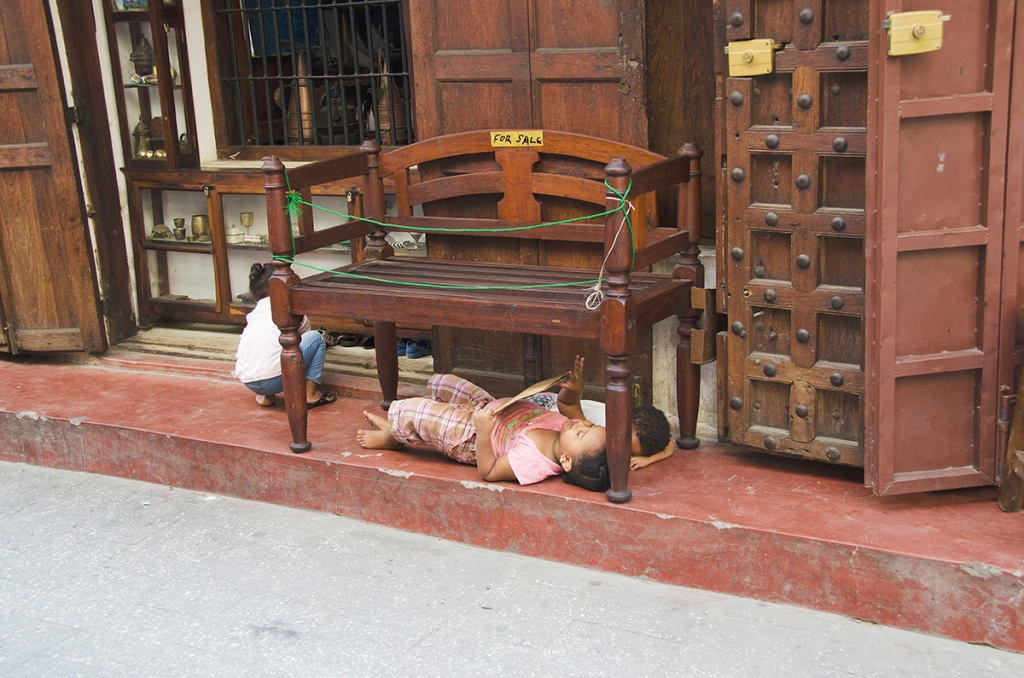 Zanzibar folding door in Gujarati style in a shop and three children at play beneath a wooden bench for sale.