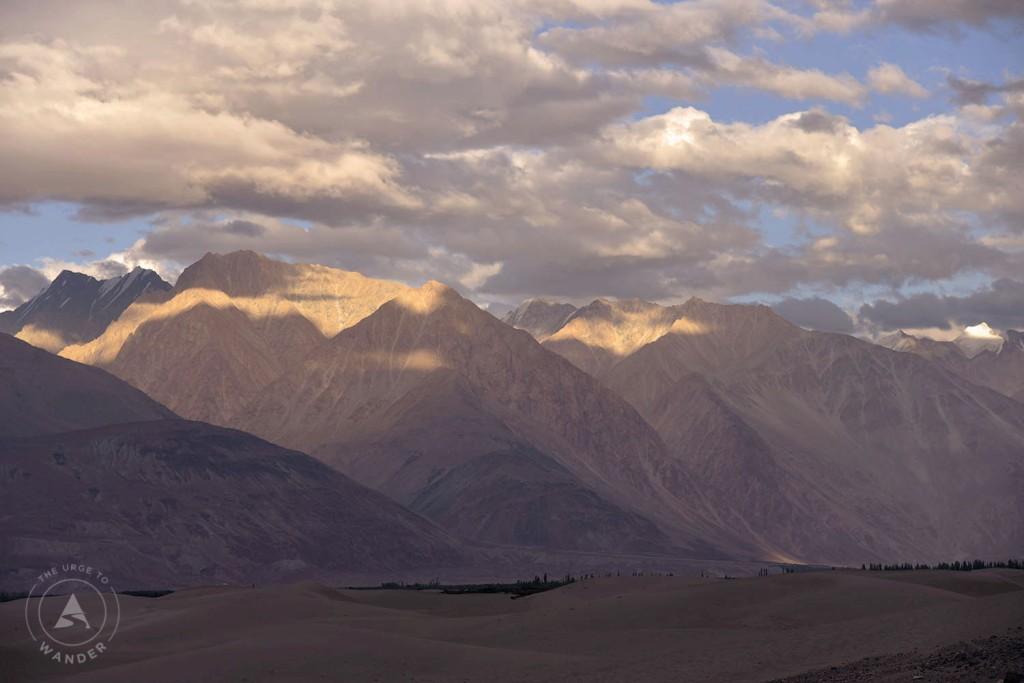 Mountain tops of the Hunder dunes illuminated at dusk.