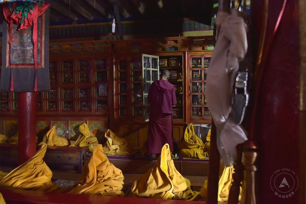 Likir Monastery - a lama sorting a scripture cabinet a prayer hall.