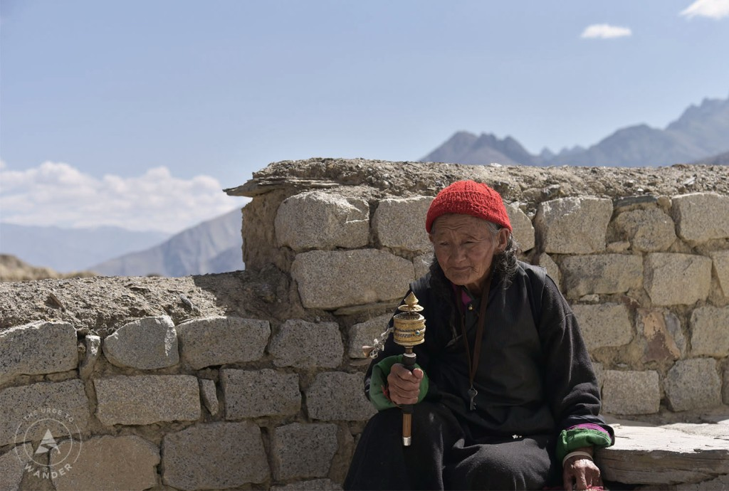 Old Buddhist nun wearing a red wool cap and holding a prayer wheel in her right hand.