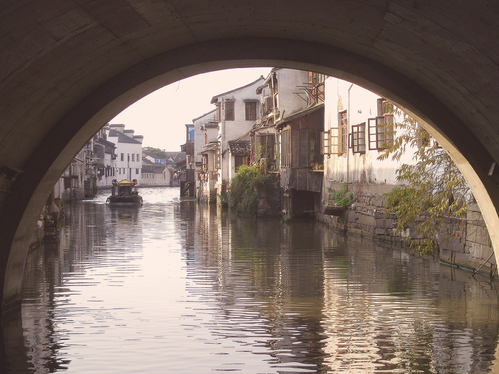 Canal-side buildings framed within an arch - boat ride, Suzhou, China