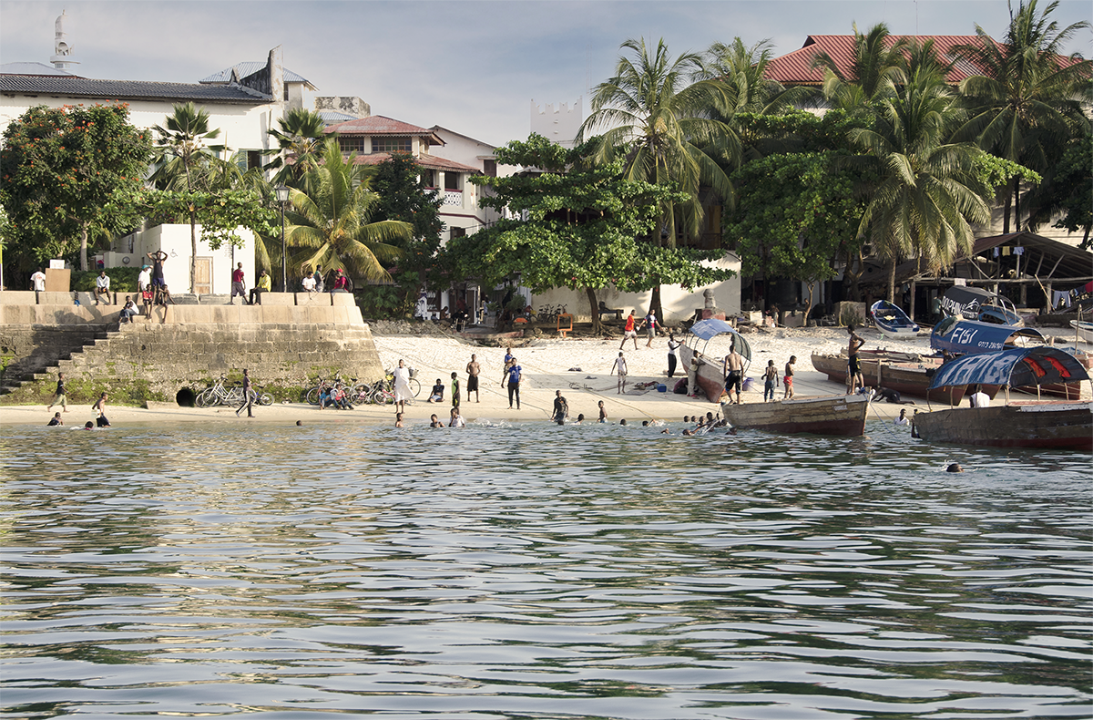 Distant view from a boat of local people on the seafront of Stone Town, Zanzibar.