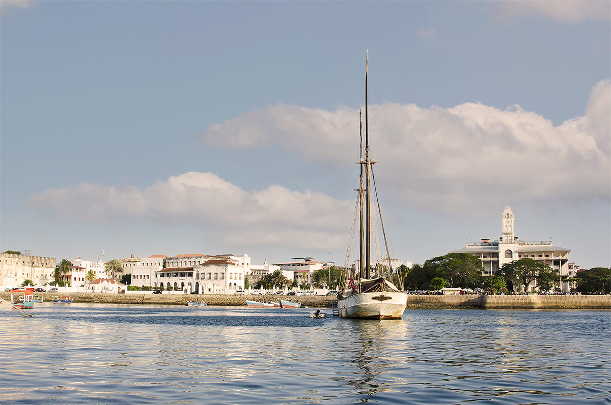 View of the Stone Town waterfront from our boat. The Palace of Wonders is on the right and the Palace museum to the left of the dhow - Stone Town Travel Guide