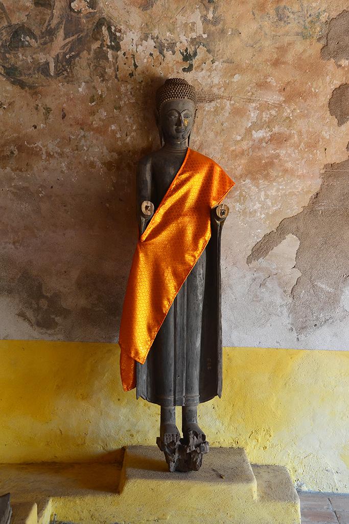 Exquisite wooden Buddha in Wat Sisaket with an orange brocade sash draped across one shoulder