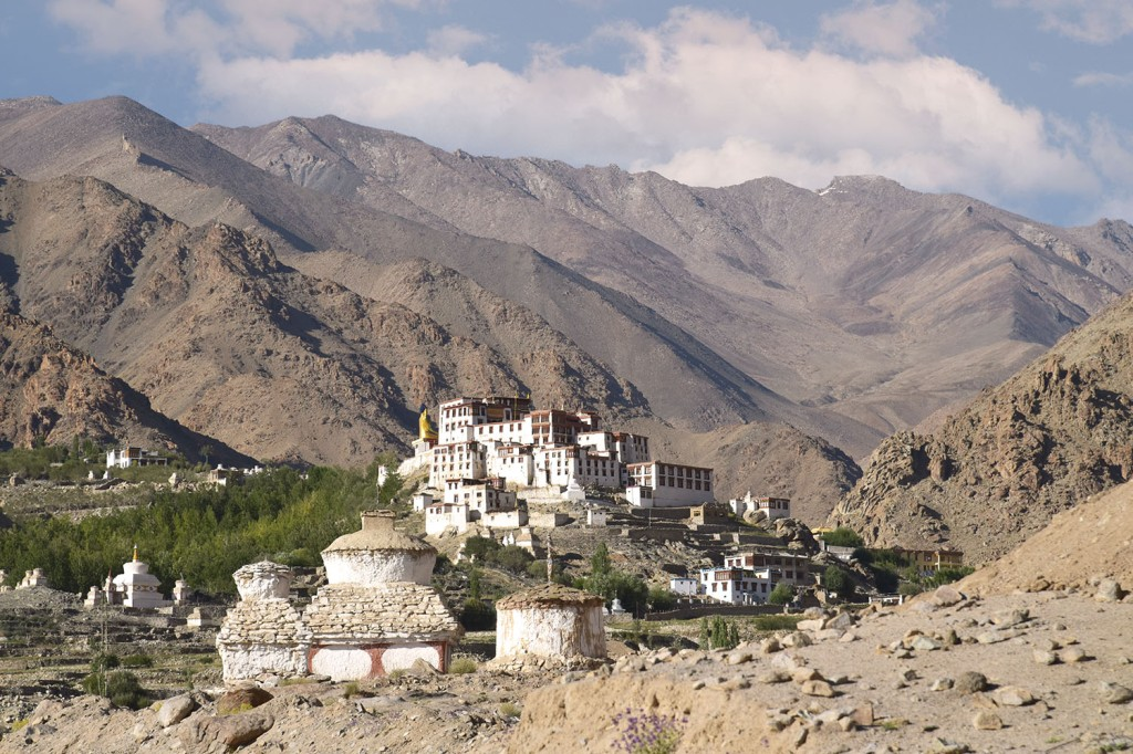 White washed buildings of Likir monastery against the barren brown mountain backdrop.
